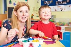 Profesor Helping Preschool Child en Art Class Foto de archivo