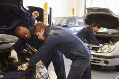 Profesor Helping Student Training a ser mecánicos de coche Imágenes de archivo libres de regalías