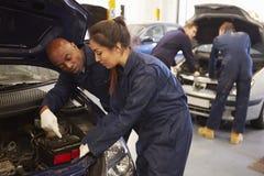 Profesor Helping Student Training a ser mecánicos de coche Imagen de archivo