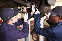 Profesor Helping Student Training a ser mecánicos de coche Imagen de archivo libre de regalías