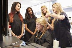 Profesor Helping Students Training a hacer peluqueros foto de archivo libre de regalías