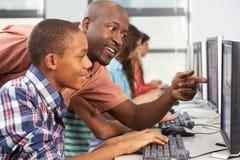 Profesor Helping Students Working en los ordenadores en sala de clase fotos de archivo