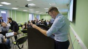 Profesor hermoso en la camisa blanca que se prepara para comenzar la presentación delante de estudiantes en sala de clase metrajes