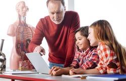 Profesor implicado brillante que consulta a sus estudiantes Imágenes de archivo libres de regalías