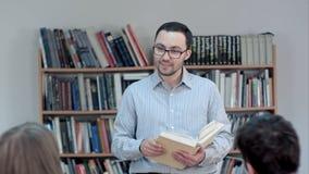 Profesor joven con el libro en manos en sala de clase de la escuela que habla con la clase fotografía de archivo