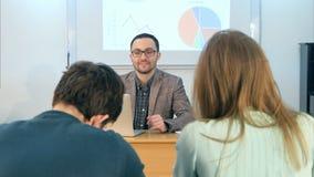 Profesor joven que se sienta en sala de clase de la escuela con el ordenador portátil, hablando con los estudiantes Imágenes de archivo libres de regalías