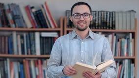 Profesor joven que sostiene el libro y que mira la cámara fotos de archivo libres de regalías