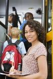 Profesor Loading Elementary Students en el autobús escolar imagenes de archivo