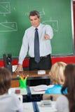 Profesor maduro Pointing At Students Imágenes de archivo libres de regalías