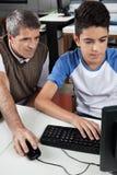 Profesor With Male Student que usa el ordenador en el escritorio Foto de archivo
