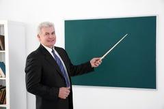 Profesor mayor con el indicador que coloca la pizarra cercana Foto de archivo