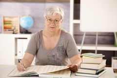 Profesor mayor en la escuela que busca en un libro Imagenes de archivo