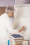 Profesor mayor que drena fórmulas moleculares Fotos de archivo libres de regalías