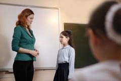 Profesor mayor sonriente cerca de la pizarra que pregunta a estudiante imagen de archivo