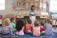Profesor At Montessori School que lee a los niños en el tiempo de la historia Fotografía de archivo libre de regalías