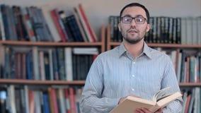 Profesor o profesor particular positivo que habla TA una cámara, sosteniendo un libro en sus manos fotos de archivo