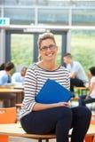 Profesor particular de sexo femenino Sitting In Classroom con la carpeta Fotos de archivo libres de regalías
