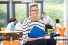Profesor particular de sexo femenino Sitting In Classroom con la carpeta fotos de archivo