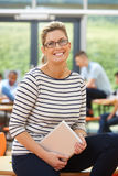 Profesor particular de sexo femenino Sitting In Classroom con la tableta de Digitaces Fotografía de archivo libre de regalías