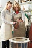 Profesor particular With Female Student en florero de la leña del estudio de la cerámica en horno Imagenes de archivo