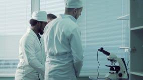 Profesor particular que muestra el microscopio electrónico almacen de video
