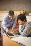 Profesor pomaga ucznia w sala lekcyjnej zdjęcie stock