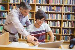 Profesor pomaga ucznia z laptopem zdjęcie royalty free