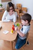 Profesor preescolar con el niño que tiene actividades educativas creativas imagenes de archivo