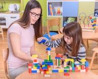 Profesor preescolar Helps Cute Girl para construir a Toy Castle Fotos de archivo libres de regalías