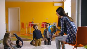Profesor preescolar que enseña a niños diversos sobre el globo almacen de video