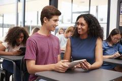 Profesor que ayuda al colegial adolescente con la tableta Fotos de archivo libres de regalías