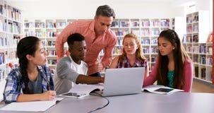 Profesor que ayuda a alumnos en el ordenador portátil 4k almacen de metraje de vídeo