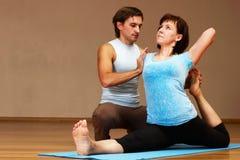 Profesor que ayuda con actitud de la yoga Foto de archivo libre de regalías