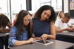 Profesor que ayuda a la colegiala adolescente con la tableta imagen de archivo