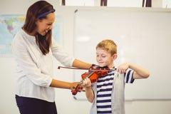 Profesor que ayuda a un colegial para tocar un violín en sala de clase Foto de archivo libre de regalías