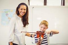 Profesor que ayuda a un colegial para tocar un violín en sala de clase Fotos de archivo libres de regalías