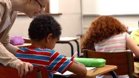 Profesor que ayuda a un niño pequeño durante clase metrajes
