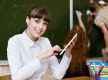 Profesor que celebra una tableta en la sala de clase mirada del camer Fotografía de archivo libre de regalías