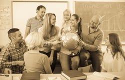 Profesor que consulta a diversos estudiantes de la edad imagen de archivo