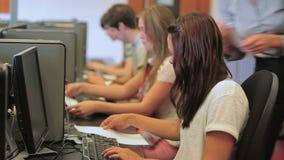 Profesor que da documentos a los estudiantes en una clase del ordenador metrajes