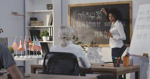 Profesor que da la lección china en una sala de clase metrajes