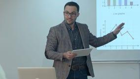 Profesor que da la lección a los estudiantes que usan la tableta digital en sala de clase Foto de archivo