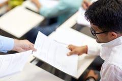 Profesor que da la prueba del examen al estudiante en la conferencia imagen de archivo libre de regalías