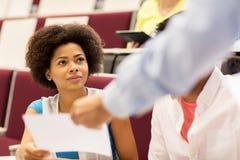 Profesor que da la prueba a la muchacha del estudiante en conferencia Imagen de archivo libre de regalías