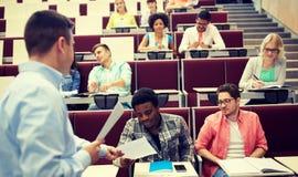 Profesor que da pruebas a los estudiantes en la conferencia imagenes de archivo