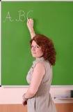 Profesor que escribe el ABC en un tablero en la escuela Fotos de archivo