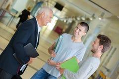 Profesor que habla con los estudiantes en vestíbulo Foto de archivo libre de regalías
