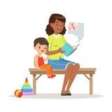 Profesor que lee un libro al niño pequeño mientras que se sienta en un banco, una educación de los niños y una educación en prees Foto de archivo