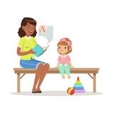 Profesor que lee un libro a la niña que se sienta en un banco, una educación de los niños y una educación en preescolar o guarder Foto de archivo