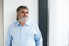 Profesor que se coloca al lado de una ventana Imagenes de archivo